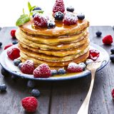Pancakes with honey and berries on white background royalty free stock image