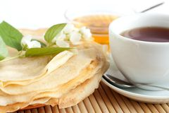 Pancakes with honey and black tea in a white cup. Jasmine flowers on top of pancakes Stock Photography