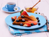 Pancakes and honey dipper on blue wooden Royalty Free Stock Images