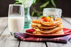 Pancakes with honey, fruit and glass of milk Royalty Free Stock Photos