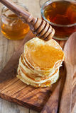 Pancakes with honey. Homemade pancake with honey on olive wooden plate. Selective focus Royalty Free Stock Photos