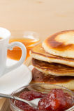 Pancakes with honey and jam and white cup of tea Stock Photography