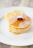 Pancakes with honey and lemon on plate Stock Images