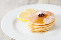 Pancakes with honey and lemon on plate Stock Photos