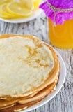 Pancakes, honey and lemons Stock Photography