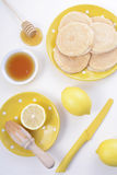 Pancakes, honey and lemons Stock Images
