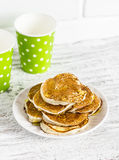 Pancakes with honey and milk in paper cups on white wooden table. Royalty Free Stock Photo