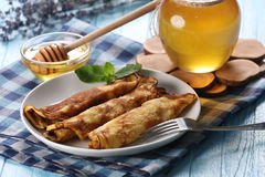 Pancakes with honey on a plate, the honey in a glass bowl and la royalty free stock image