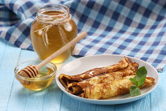 Pancakes with honey on a plate, the honey in a glass bowl Stock Photography