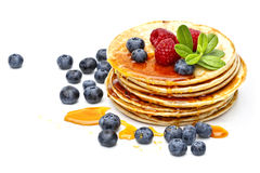 Pancakes with honey, raspberries and bilberries Royalty Free Stock Image