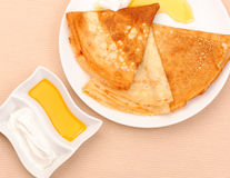 Pancakes with honey and sour cream. Royalty Free Stock Photos