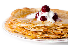 Pancakes with honey, sour cream and cherry Royalty Free Stock Image