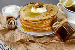 Pancakes with honey and sour cream and walnuts on a paper napkin Royalty Free Stock Image