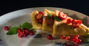 Pancakes with honey strawberries and currants in a plate Royalty Free Stock Photo