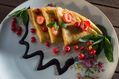 Pancakes with honey strawberries and currants in a plate Royalty Free Stock Photos