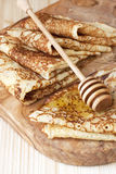 Pancakes with honey on wooden board Royalty Free Stock Photos