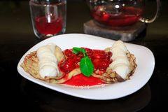 Pancakes with ice cream drizzled with strawberry and mint, teapo royalty free stock photography