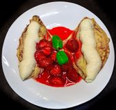 Pancakes with ice cream drizzled with strawberry royalty free stock photography