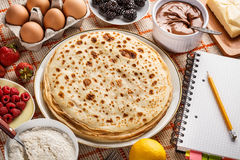 Pancakes. Ingredients and recipe book for pancakes on kitchen table Stock Photography