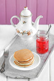 Pancakes with jam. Pancakes with red jam in a glass jar stock images