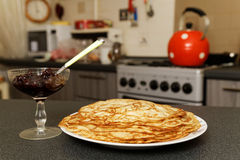 Pancakes and jam on the background of the kitchen Royalty Free Stock Images