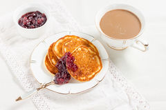 Pancakes with jam and coffee on a white table Stock Image