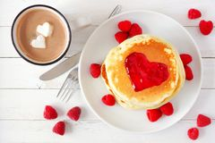 Love concept breakfast pancakes, hot chocolate and raspberries over white wood. Pancakes with jam in shape of heart and hot chocolate with marshmallow hearts Royalty Free Stock Photography