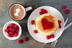 Love concept breakfast pancakes, hot chocolate and raspberries over slate. Pancakes with jam in shape of heart, hot chocolate and raspberries over a slate Stock Photography