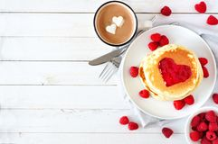 Love concept breakfast with pancakes, hot chocolate and raspberries over white wood. Pancakes with jam in shape of heart, hot chocolate and raspberries over Stock Image