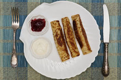 Pancakes with jam and sour cream. Three pancakes with sour cream and jam served on seashell styled crockery with silverware royalty free stock photo