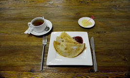 Pancakes with jam and tea. Pancakes with berry jam, cup of tea and lemon Stock Image