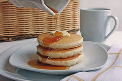 Pancakes for Lunch. Syrup bring poured onto a plate of stacked pancakes with butter Royalty Free Stock Photography