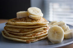 Pancakes with maple syrup and bananas. Picture of homemade pancakes served with maple syrup and sliced bananas royalty free stock photography