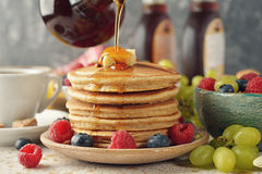 Pancakes with maple syrup and berries. On a brown background stock images