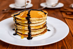 Pancakes with maple syrup. Traditional american breakfast pancakes with maple syrup and chocolate royalty free stock photography
