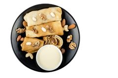 Pancakes with nuts and condensed milk on black plate isolated on white background. Top view stock photos