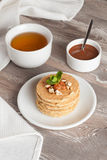 Pancakes with nuts, decorated mint for breakfast, vertical. Close up Stock Photography