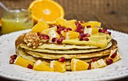 Pancakes with orange curd. Orange slices and pomegranate, on a wooden table Royalty Free Stock Photography