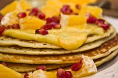 Pancakes with orange curd. Orange slices and pomegranate, on a wooden table stock photos