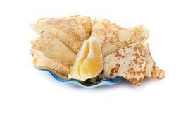 Pancakes with an orange lobule. Thin pancakes with an orange lobule are isolated on a white background Stock Photos