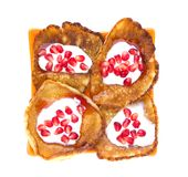 Fritters on a white background on a plate. Pancakes on an orange plate with sour cream, jam and pomegranate Royalty Free Stock Image