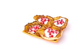 Fritters on a white background on a plate. Pancakes on an orange plate with sour cream, jam and pomegranate Stock Photos