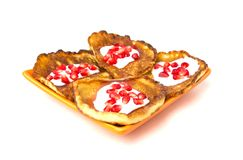 Fritters on a white background on a plate. Pancakes on an orange plate with sour cream, jam and pomegranate Stock Photography