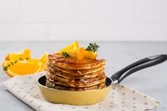Pancakes with orange and sprinkled maple syrup in a small yellow pan on white background. Breakfast stock image