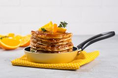 Pancakes with orange and sprinkled maple syrup in a small yellow pan on white background. Breakfast royalty free stock photography