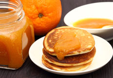 Pancakes with oranges and orange jam in glass jar. Royalty Free Stock Images