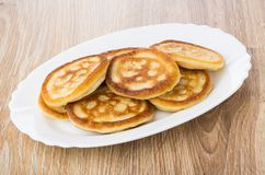 Pancakes in oval white dish on table Royalty Free Stock Images