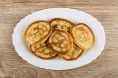 Pancakes in oval white dish on wooden table Royalty Free Stock Photography