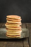 Pancakes. Piled up on dark wooden background stock image