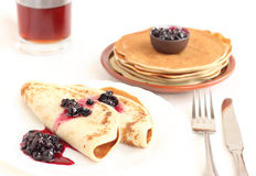 Pancakes on a plate with black currant jam Stock Images